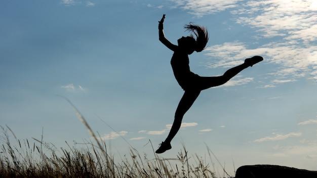 Silhouet van een gracieuze turnster of acrobaat met een welgevormde figuur die hoog opspringt tegen een blauwe avondlucht