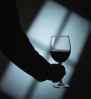 Silhouet van een hand met wijn en schaduwen