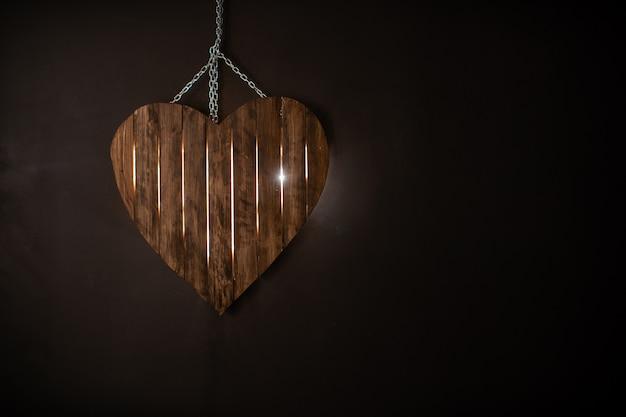 Silhouet van een hart gemaakt van hout met verlichting op een donkere achtergrond. vrije ruimte