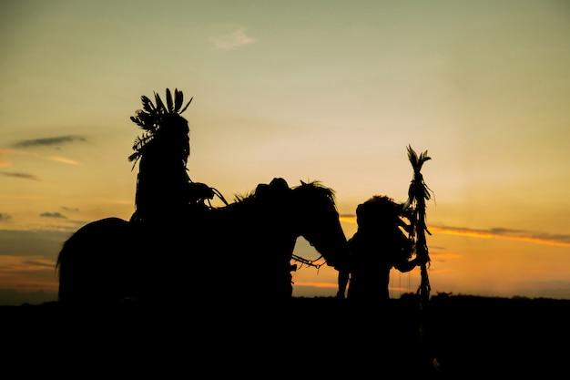 Silhouet van een indiase man op een paard bij zonsondergang