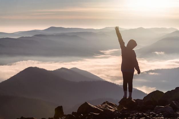 Silhouet van een jong meisje op een bergtop met een opgeheven hand boven lage wolken bij dageraad. succes en overwinning concept.