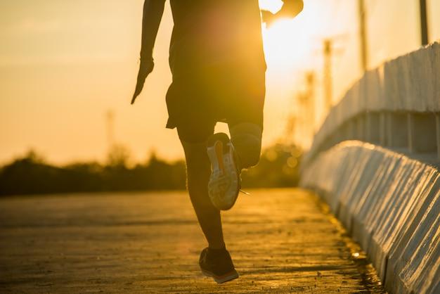 Silhouet van een jonge fitness man loopt op zonsopgang