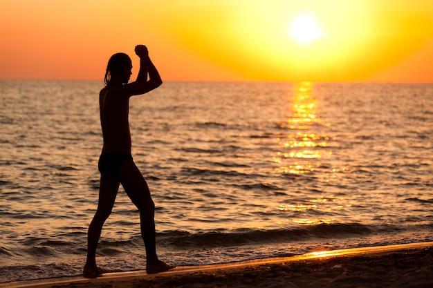Silhouet van een jonge man die langs de rand van het zeewater loopt tijdens een kleurrijke gouden zonsondergang