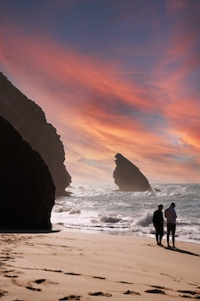 Silhouet van een jonge man en vrouw, paar, kijken naar de zee tijdens zonsondergang in praia de adraga portugal.