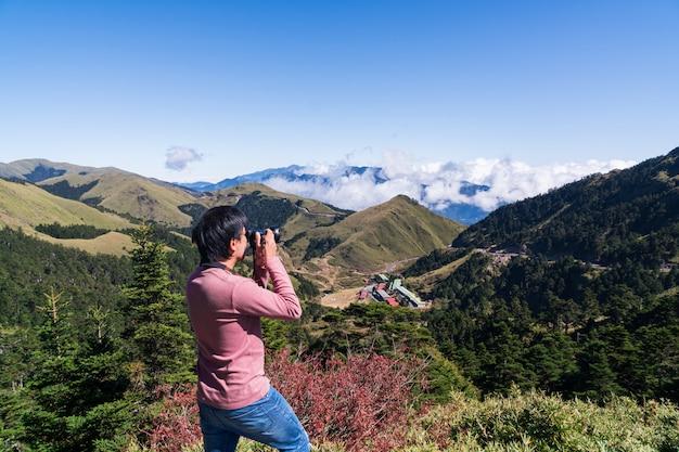 Silhouet van een jonge man in een roze t-shirt met lange mouwen, genietend van het geweldige uitzicht en maak een foto bovenop de berg