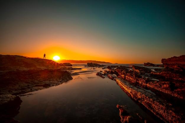 Silhouet van een jonge man met armen omhoog op de rotsen van hendaye bij een zonsondergang