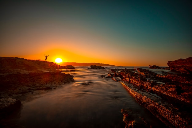 Silhouet van een jonge man met armen omhoog op de rotsen van hendaye bij een zonsondergang Premium Foto