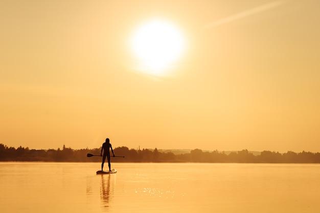 Silhouet van een jonge man met atletisch lichaam die lange peddel met twee handen vasthoudt terwijl hij op sup board staat.