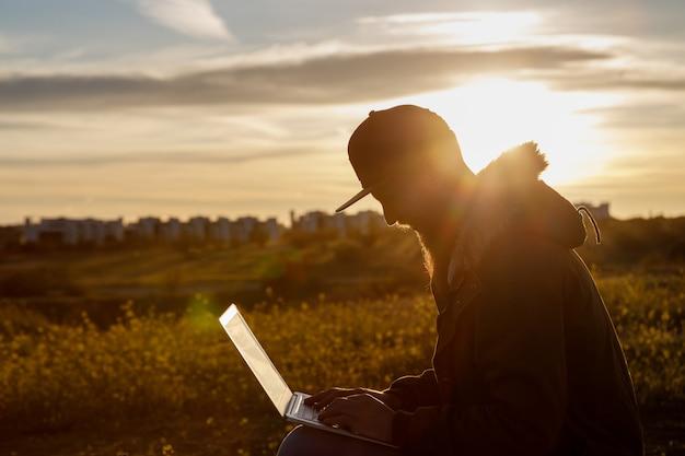 Silhouet van een jonge man met een baard die met zijn laptop werkt bij zonsondergang in de natuur