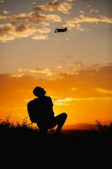 Silhouet van een jonge man met een rugzak die een drone in een landelijke omgeving op zonsondergang bestuurt