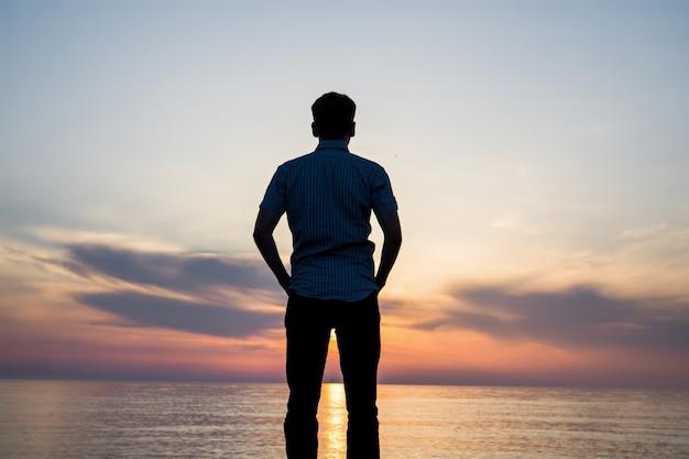 Silhouet van een jonge man op het strand bij zonsondergang