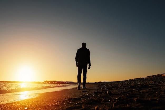 Silhouet van een jonge man op het strand in italië.
