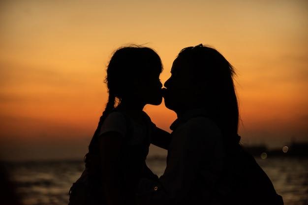 Silhouet van een jonge moeder die veel liefs haar dochtertje kust