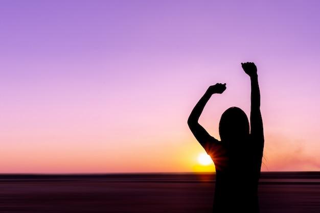 Silhouet van een jonge vrouw bij zonsondergang op zee achtergrond.