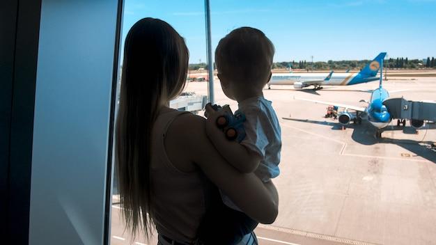 Silhouet van een jonge vrouw die haar zoon vasthoudt en op vliegtuigen kijkt door het raam op de luchthaventerminal.