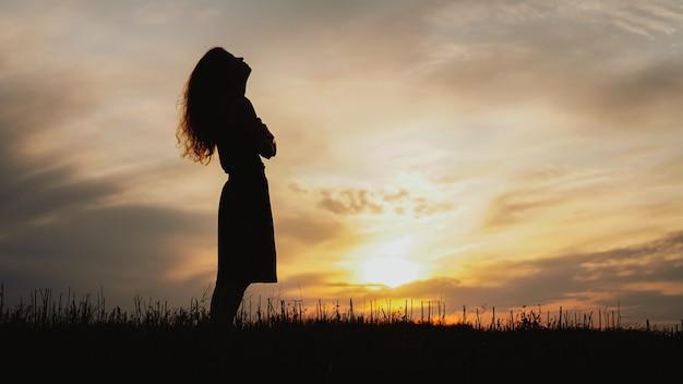 Silhouet van een jonge vrouw die permanent in droog grasveld op heldere zonsondergang