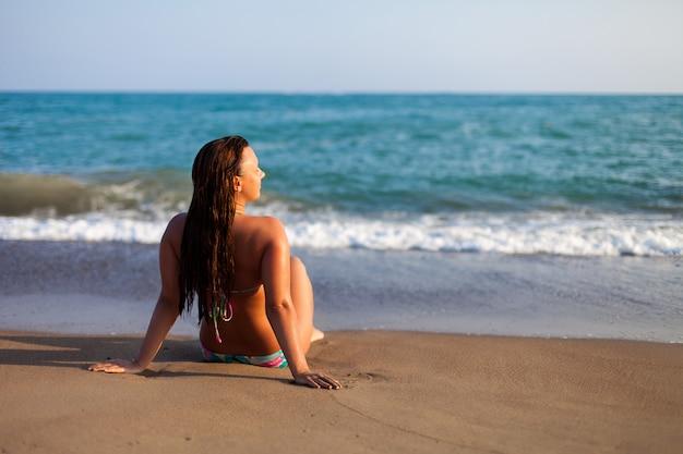 Silhouet van een jonge vrouw op strand.