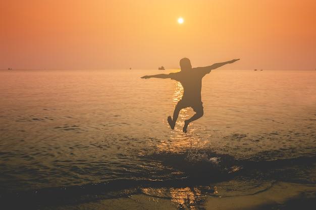 Silhouet van een jongen staande yogahouding op het strand