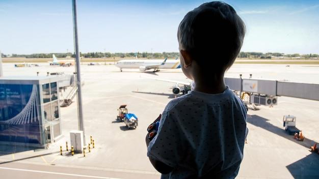 Silhouet van een kleine jongen die door het raam op de landingsbaan van de luchthaven kijkt.