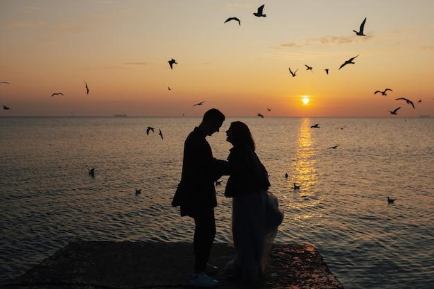 Silhouet van een liefdevol paar bij zonsondergang met zee en vliegende meeuwen op de achtergrond.