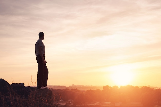 Silhouet van een man bij de zonsondergang op de berg