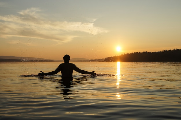 Silhouet van een man bij zonsondergang achtergrond. de man op de taille dook in de zee.
