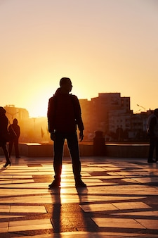 Silhouet van een man bij zonsondergang in de winter, casablanca, marokko. de zon gaat onder achter de man. de zonnestralen zijn goudgeel. marokko, casablanca, 18 december 2017