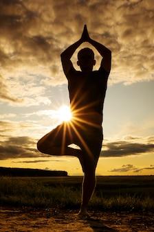 Silhouet van een man die aan yoga doet