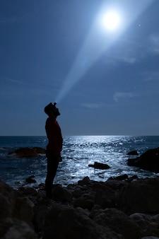 Silhouet van een man die de maan verlicht