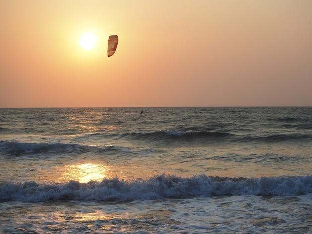 Silhouet van een man die in de zee rijdt op kitesurfen in de stralen van de ondergaande zon. extreme watersporten