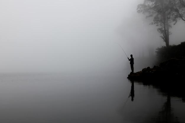 Silhouet van een man die op het meer met dikke mist op de achtergrond vist