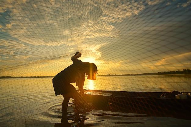 Silhouet van een man die traditionele thaise traditionele visserij in de rivier doet. in chiang mai, thailand 12/05/2021