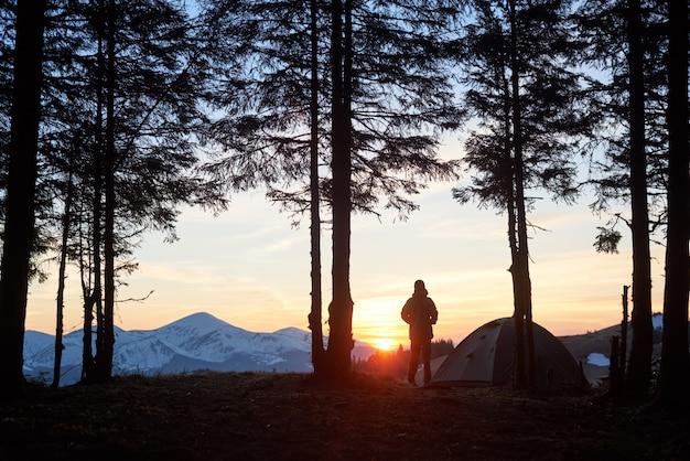Silhouet van een man die zich bovenop een berg bevindt die van mooi natuurlijk landschap geniet