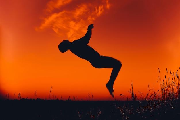 Silhouet van een man doet een back flip bij zonsondergang