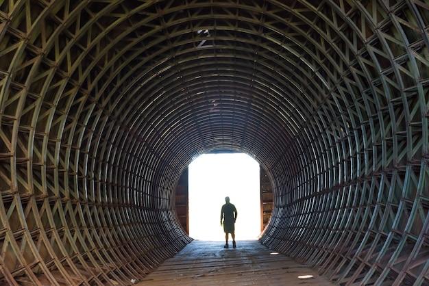 Silhouet van een man en licht aan het einde van de donkere tunnel