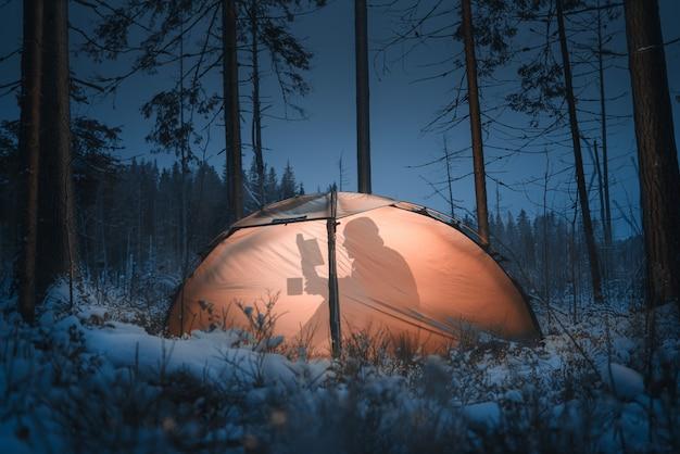 Silhouet van een man in een tent. hij leest een boek en drinkt thee. wintertijd. dennenbos