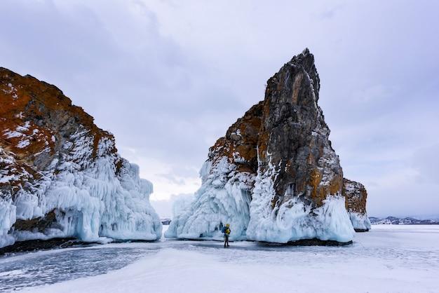 Silhouet van een man in gele jas met rugzak staat in de buurt van twee rotsen bedekt met ijspegels. baikalmeer bij bewolkt weer.
