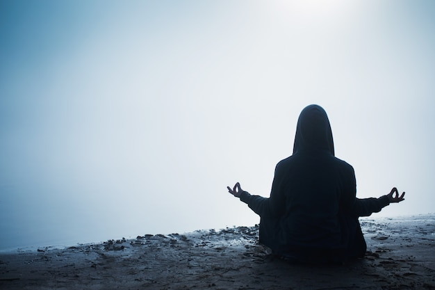 Silhouet van een man in het donker. yoga meditatie. lotus positie. silhouet van man in kap. donkere schaduw. meditatie in lotus houding. yoga voor mentale gezondheid. leven concept. ontspanning op de ochtend natuur