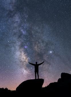 Silhouet van een man kijken naar de nachtelijke hemel