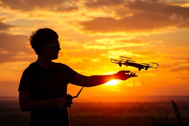 Silhouet van een man lanceert een drone met een afstandsbediening in het zonsonderganglicht