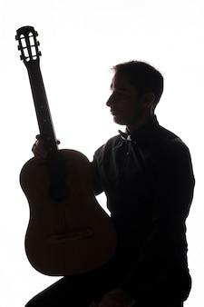 Silhouet van een man met akoestische gitaar