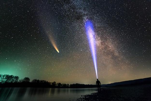 Silhouet van een man met een hoofdzaklamp die op de oever van de rivier staat te loeren op neowise-komeet in de donkere nachtelijke hemel.