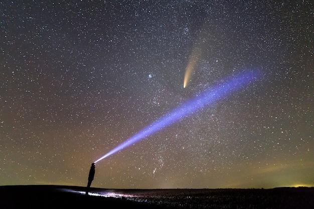 Silhouet van een man met een zaklamp op zijn hoofd die een heldere lichtstraal op de sterrenhemel richt met een neowise-komeet met een lichte staart.