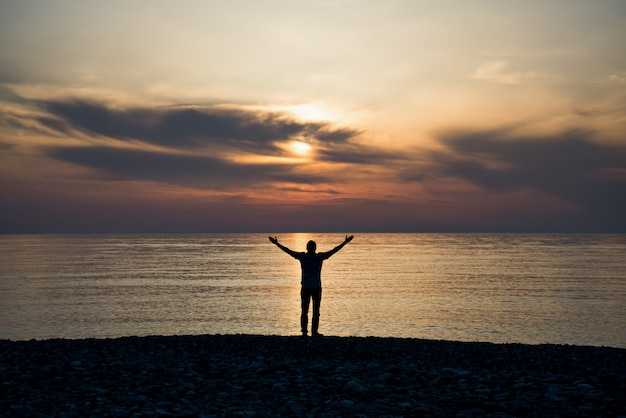 Silhouet van een man met opgeheven armen in het zeewater bij zonsondergang