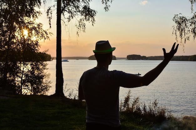 Silhouet van een man met zijn hand opgeheven tegen de ondergaande zon