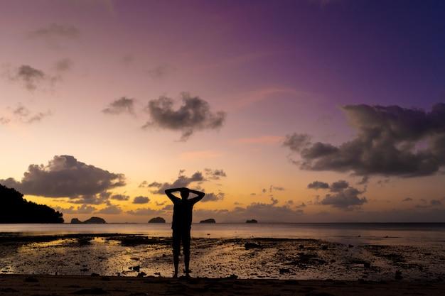 Silhouet van een man op het strand bij zonsondergang. de mens verheugt zich en ontmoet de zonsondergang