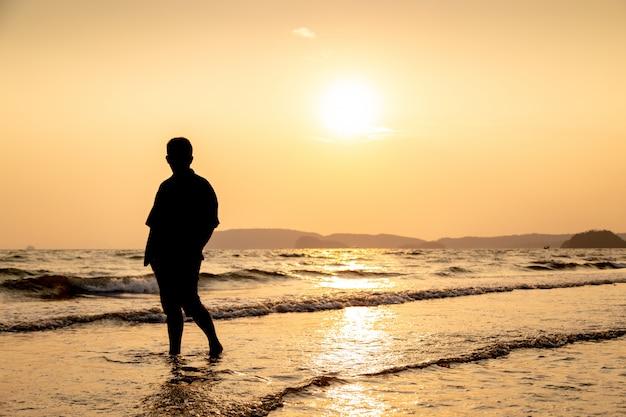 Silhouet van een man op het strand bij zonsondergang.