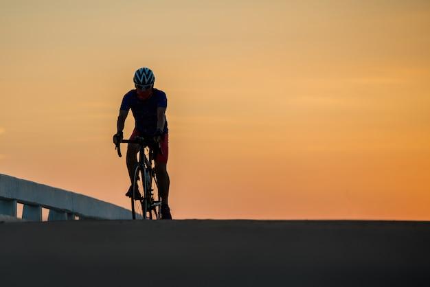 Silhouet van een man rijdt op een fiets bij zonsondergang. oranje-blauwe hemelachtergrond.