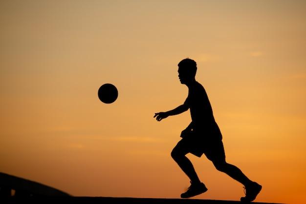 Silhouet van een man voetballen in gouden uur, zonsondergang.