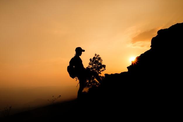 Silhouet van een man wandelaar op de top van de heuvel